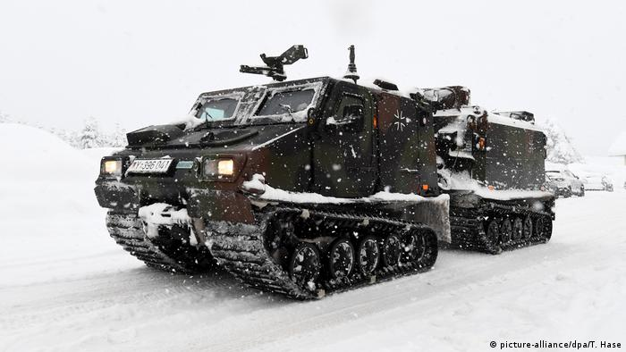 A tracked vehicle of the Bundeswehr drives over a snow-covered road
