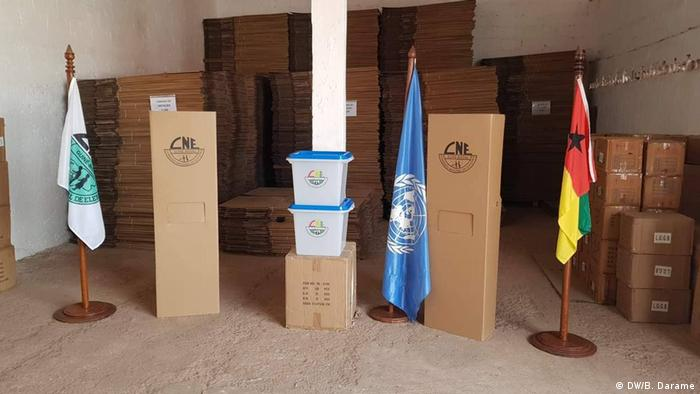 Boxes with election material - next to them, the UN and the national flag (DW/B. Darame)
