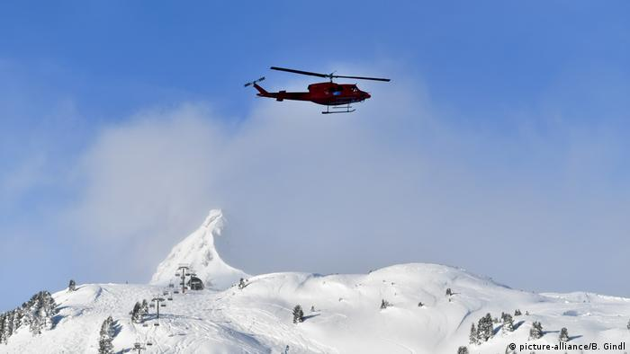 A helicopter flying over the Alps