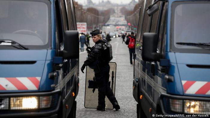 A police officer between two police vans on the Champs-Elysees in Paris