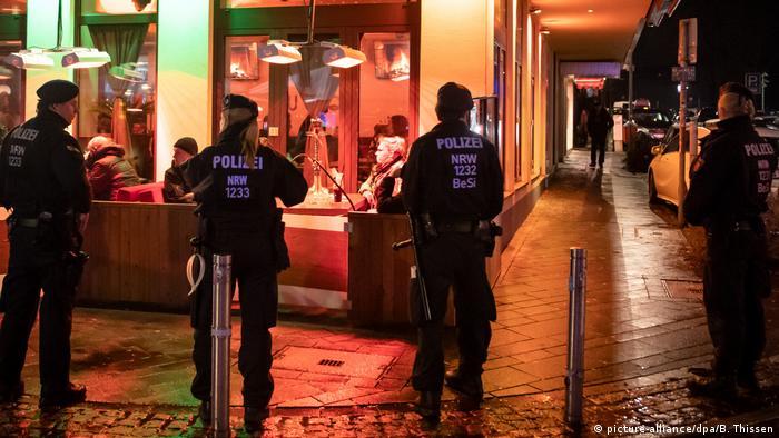 Police stand outside a shisha bar in Bochum