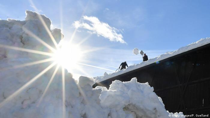 Men clear a roof of snow