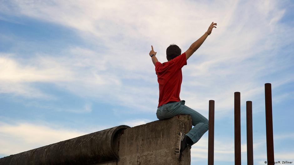 Deutschland Checkpoint Charlie Berlin | Junger Mann auf Mauer