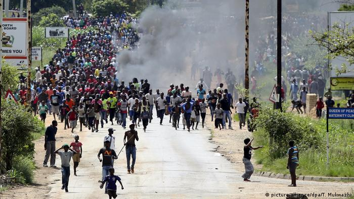 A crowd of protesters run down the street in Harare