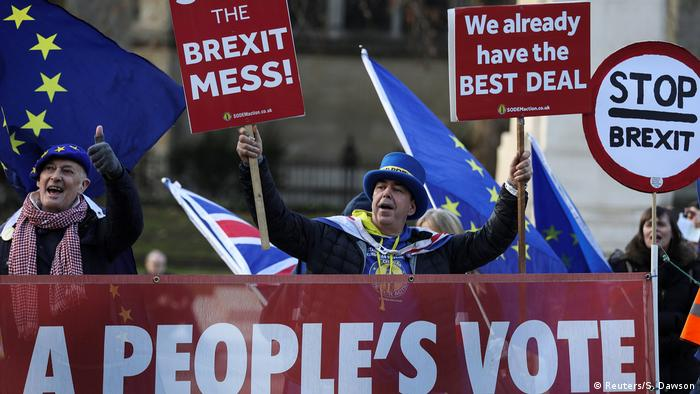 Anti-Brexit protesters hold signs outside the Houses of Parliament