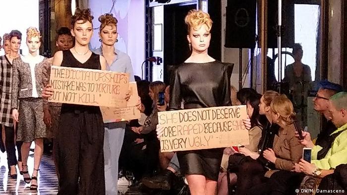 Bei der Runway Show der Designerin Aline Celi tragen Models Protestschilder vor sich her. (DW/M. Damasceno)