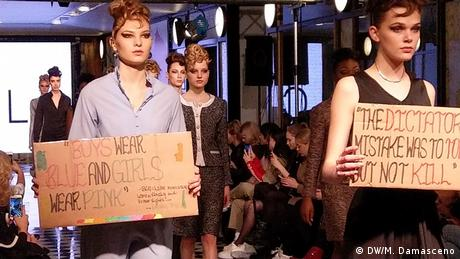 Models on the runway at the Aline Celi show in Berlin carry protest placards(DW/M. Damasceno)