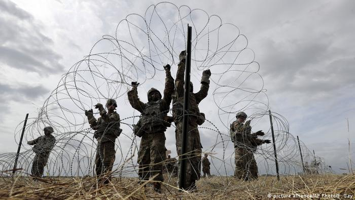 US troops deployed to the US-Mexico border put up razor wire near a border encampment