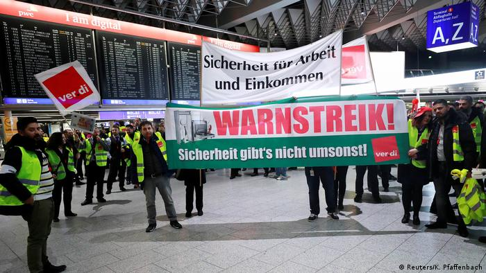 Security personnel at Frankfurt airport hold a banner that says: Security isn't free of charge. (Reuters/K. Pfaffenbach)