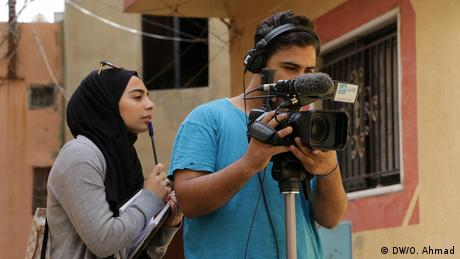 We're doing a story on migration and have come to the Al-Jahil refugee camp to do the filming. We've chosen the topic because people are leaving the camps to start new lives in other countries. Samih's responsible for the technical side here and I'm focusing on the content. (DW/O. Ahmad)
