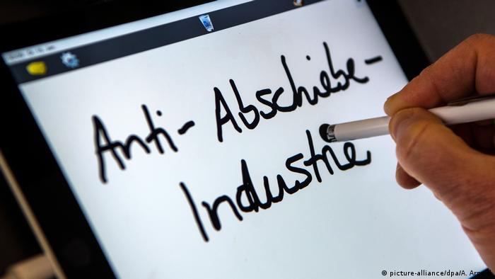 Eine Hand schreibt auf einen Bildschirm das Unwort des Jahres 2018 Anti-Abschiebe-Industrie.