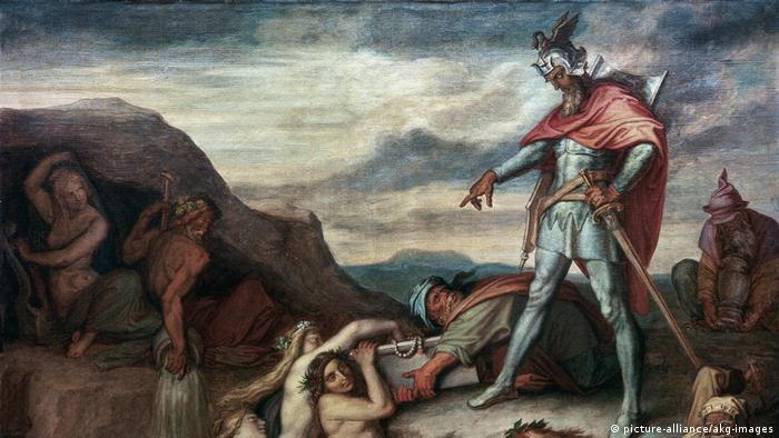 Man in armor directs vassels to hand over a chest to naked mermaids on the rocky side of a riverbed (picture-alliance/akg-images)