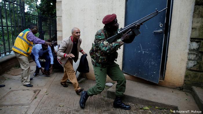 A member of the Kenyan military forces points his gun upwards as civilians follow behind, crouching down