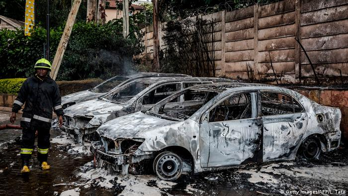 A fireman stands on the left side of a group of burnt-out cars