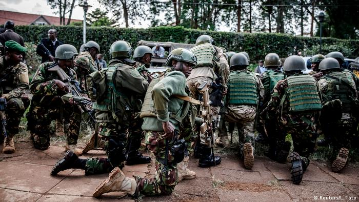 A group of Kenyan special forces crouch on the ground as the terror attack is underway