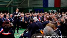 French President Emmanuel Macron (L) delivers a speech during a meeting gathering some 600 mayors who will relay the concerns aired by residents in their towns and villages in the Normandy city of Grand Bourgtheroulde on January 15, 2019, as part of the official launch of the great national debate, a central plank of French President Emmanuel Macron bid to turn around his embattled presidency since the yellow vest (gilet jaune) movement protests. - The meeting sounds the start of two months of public consultations in towns and villages across the country on four main themes: taxation; France's transition to a low-carbon economy; democracy and citizenship, and the functioning of the state and public services. (Photo by PHILIPPE WOJAZER / POOL / AFP) (Photo credit should read PHILIPPE WOJAZER/AFP/Getty Images)