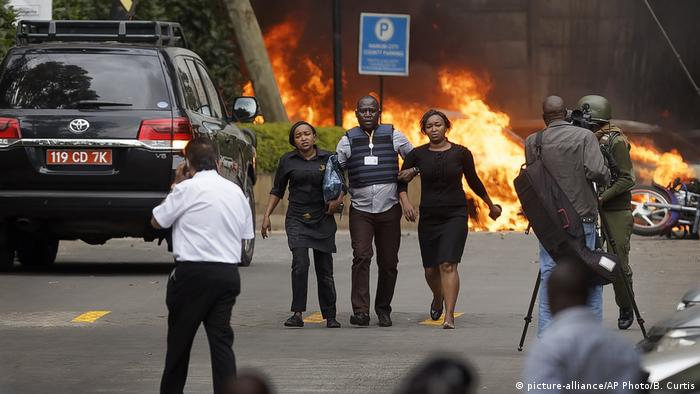 A security guard escorts two women from a burning hotel