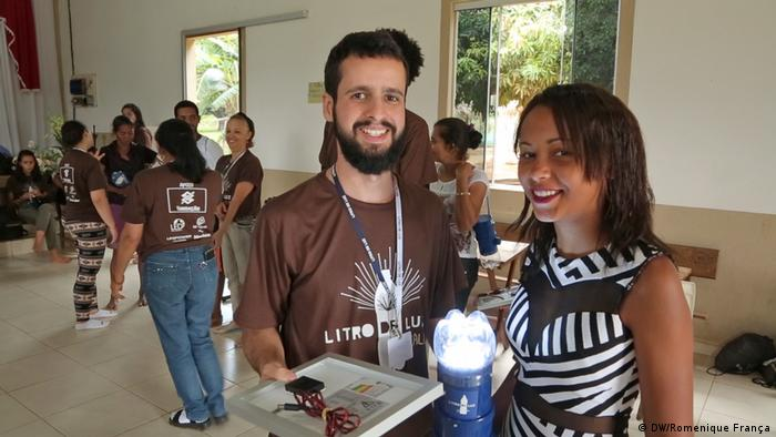 Male and female NGO workers with a solar powered lamp made from a plastic bottle