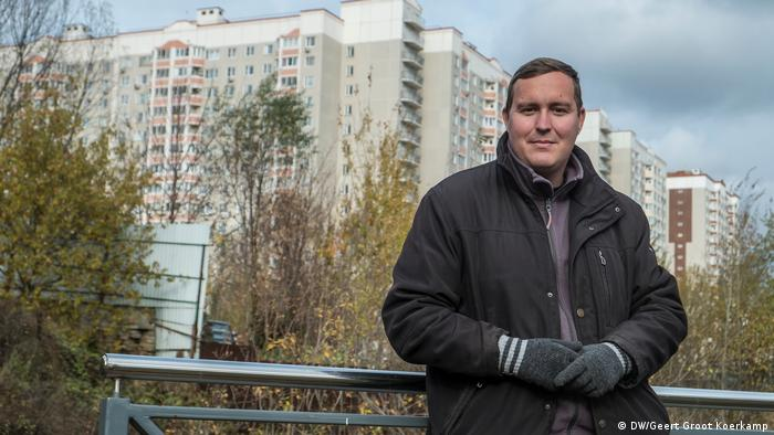 Ilya Sorokin stands on a bridge in the village of of Pykhtino. In the background newly-built high-rise buildings are visible