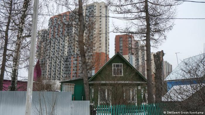 A small building in front of high-rises