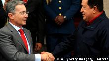 Venezuelan President Hugo Chavez (R) shakes hands with his Colombian counterpart Alvaro Uribe upon arrival at the Miraflores presidential palace in Caracas on April 14, 2009. Uribe is in Venezuela to sign bilateral agreements on oil and gas matters. AFP PHOTO/Juan Barreto (Photo credit should read JUAN BARRETO/AFP/Getty Images)