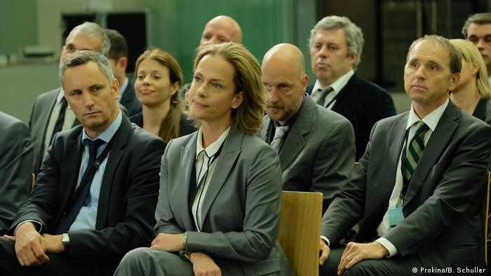People seated in an audience, in this film still featuring Claudia Michelsen