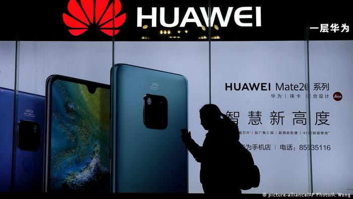 A woman browses her smartphone as she walks by a Huawei store