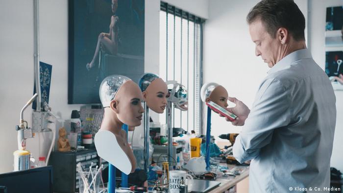 Ein Mann steht in einem Labor weiblichen Robotergesichtern gegenüber und schaut auf sein Handy.