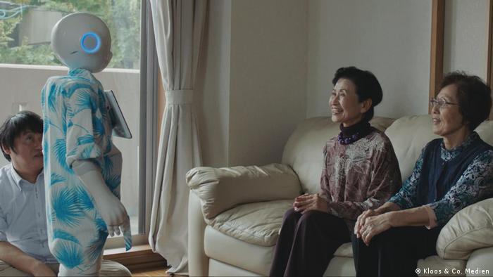Zwei japanische Frauen sitzen auf einem Sofa, vor ihnen steht ein Roboter. Szene aus Hi, A.I von Isa Willinger.