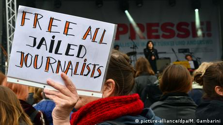 Woman at demonstration holds up sign reading 'free all jailed journalists' (picture-alliance/dpa/M. Gambarini)