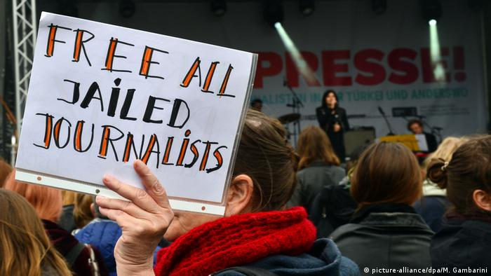 Woman at demonstration holds up sign reading 'free all jailed journalists'