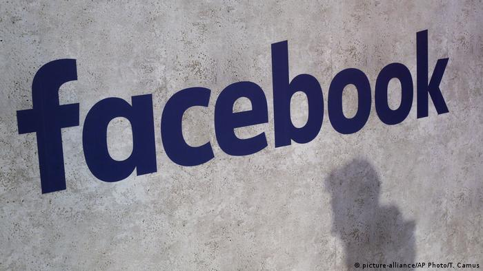 Facebook logo on a wall with the silhouette of a person underneath
