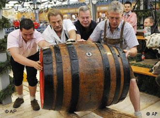 Four men push a giant keg of beer at the Oktoberfest