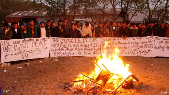 Migrants with signs around a campfire