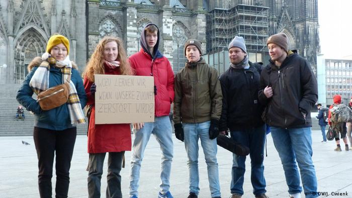 Six students stand in a row an pose for the camera during a protest in the main square next to the Cologne Cathedral.