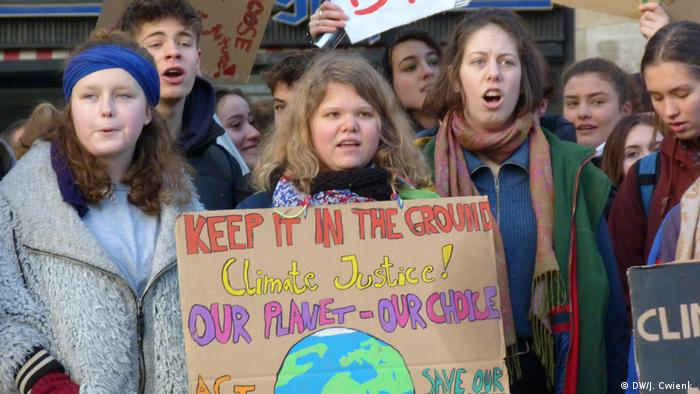 Teenagers shout as they take part in a climate protest in Cologne. The girl in the middle is wearing a cardboard sign around her neck which reads 'Keep it in the ground. Climate justice! Our planet - our choice'