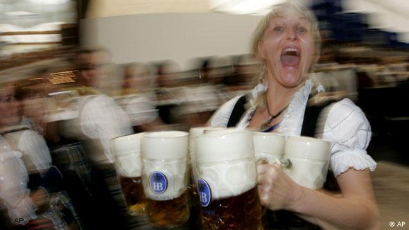 A waitress at Oktoberfest carrying five or more litre glasses of beer