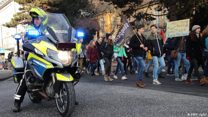 Teenagers march along a street in Bonn, Germany, carrying signs and flags to protest climate inaction. A police officer watches on from his motorbike in the foreground to the left of the frame.