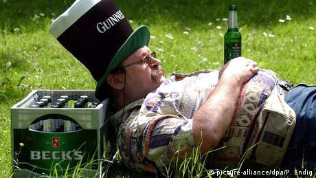 Ein Mann mit dickem Bauch und Bierflasche in der Hand liegt auf einer Wiese und lehnt sich dabei an einen Bierkasten an (picture-alliance/dpa/P. Endig)