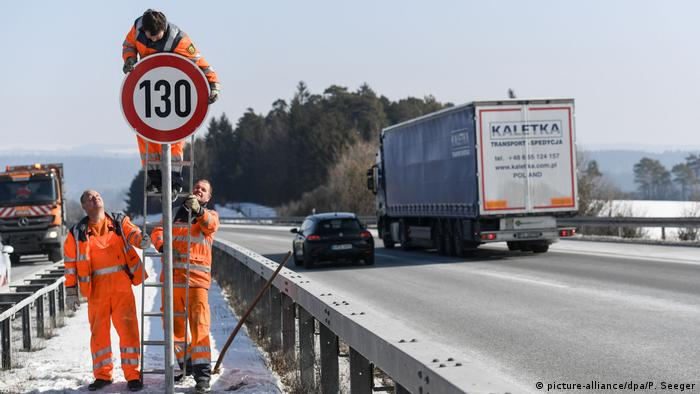 Рабочие монтируют знак ограничения скорости на автобане A81