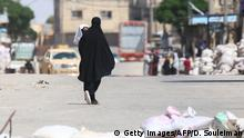 A Syrian woman carrying a child walks down a street in the town of Tabqa, about 55 kilometres (35 miles) west of Raqa city, on May 12, 2017. The Syrian Democratic Forces (SDF), an alliance of Kurdish and Arab fighters, seized the town of Tabqa and the nearby dam on May 10 after fierce fighting against the Islamic State group. / AFP PHOTO / DELIL SOULEIMAN (Photo credit should read DELIL SOULEIMAN/AFP/Getty Images)