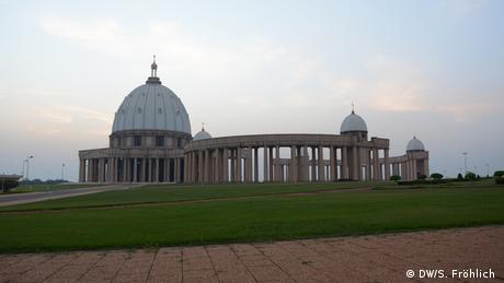 A far-off shot of the Basilica of Our Lady of Peace in Yamoussoukro, Ivory Coast. It has a domed roof with a cross on top, and pillars hold up the rest of the building. It it surrounded by green grass and empty paved pathways.
