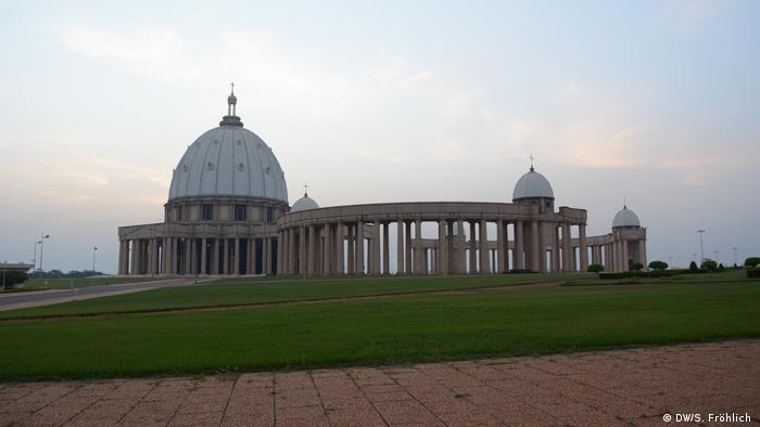 Uma foto mais distante da Basílica Nossa Senhora da Paz, em Yamoussoukro, Costa do Marfim. A igreja é cercada por grama verde e caminhos pavimentados.