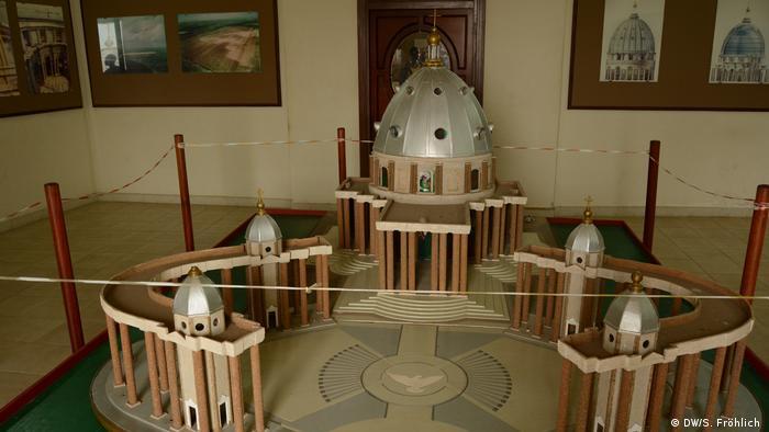 Um modelo da Basílica de Nossa Senhora da Paz, na Costa do Marfim. A réplica está em um museu, protegida por uma corda. Imagens da igreja estão nas paredes.