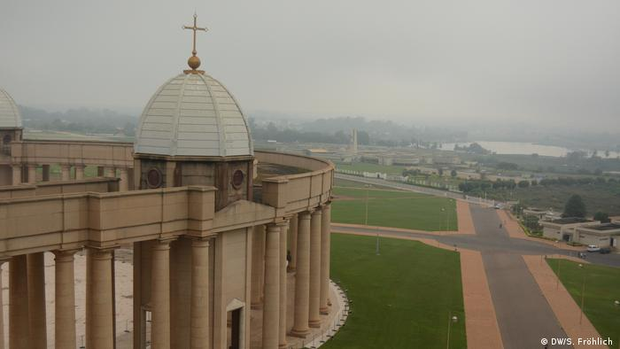 An aerial view of the Basilica of Our Lady of Peace in Ivory Coast. The church is pictured on the left of the frame next to an empty roadway and very few buildings.