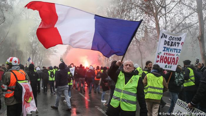 A man wearing a yellow vest waves a French flag at a protest in Paris