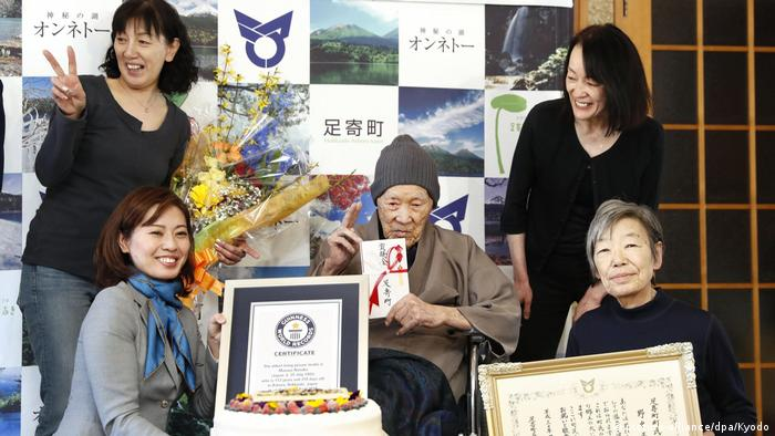 Masazo Nonaka holding a certificate recognizing him as the world's oldest man
