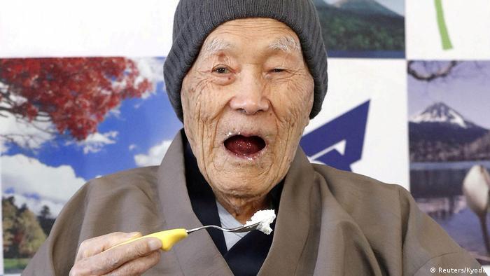 Masazo Nonaka eating his favorite cake and smiling