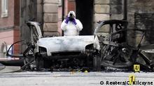 A forensic officer takes a photograph of the destroyed car in Londonderry (Reuters/C. Kilcoyne)