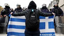 A protester holds up a Greek flag in front of police officers in Athens, Greece (Reuters/A. Avramidis)